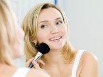 Mujer joven hermosa que hace maquillaje Foto de archivo