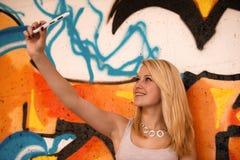 Mujer joven hermosa que hace un selfie al aire libre cerca de pintada wal Imagen de archivo libre de regalías