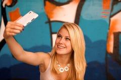 Mujer joven hermosa que hace un selfie al aire libre cerca de pintada wal Imágenes de archivo libres de regalías