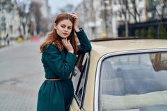 Mujer joven hermosa que hace una pausa su coche al aire libre en la ciudad Fotografía de archivo