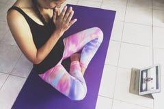 Mujer joven hermosa que hace yoga en casa y que mira el vídeo de entrenamiento en un artilugio de la tableta Muchacha que se sien Imagenes de archivo