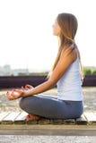 Mujer joven hermosa que hace yoga en la calle Imagen de archivo