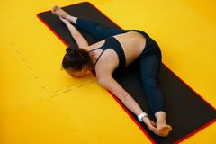 Mujer joven hermosa que hace yoga y que estira sus piernas imagen de archivo