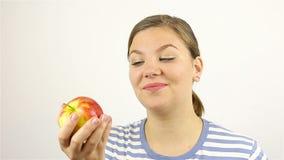 Mujer joven hermosa que huele una manzana roja almacen de metraje de vídeo