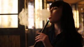 Mujer joven hermosa que inhala la cachimba shisha que fuma de la muchacha en café Primer Luz caliente almacen de video