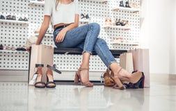 Mujer joven hermosa que intenta en los zapatos del tacón alto mientras que se sienta en el sofá en la zapatería fotografía de archivo libre de regalías