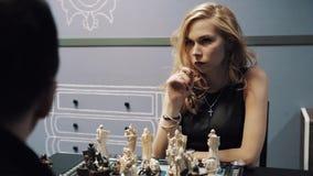 Mujer joven hermosa que juega a ajedrez con el hombre en vidrios y paseos lejos almacen de metraje de vídeo