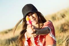 Mujer joven hermosa que juega con el arma de agua en campo Fotos de archivo