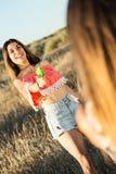 Mujer joven hermosa que juega con el arma de agua en campo Imagen de archivo libre de regalías