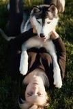 Mujer joven hermosa que juega con el perro fornido divertido al aire libre en parque en el día soleado Imagen de archivo