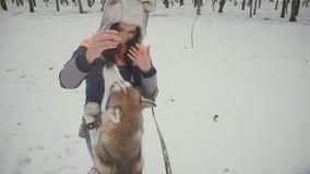 Mujer joven hermosa que juega con un perro en un parque nevoso del invierno almacen de video