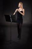 Mujer joven hermosa que juega el clarinet Foto de archivo