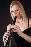 Mujer joven hermosa que juega el clarinet Imagen de archivo