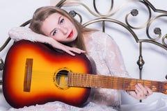 Mujer joven hermosa que juega música en una cama con felicidad y la guitarra Foto de archivo