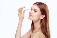 Mujer joven hermosa que la entierra ojos en un fondo blanco, farmacia Foto de archivo libre de regalías