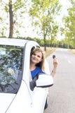 Mujer joven hermosa que le muestra llaves del coche fotografía de archivo