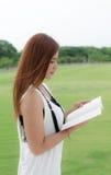 Mujer joven hermosa que lee al aire libre Imagen de archivo
