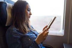 Mujer joven hermosa que lee un libro en el tren Imagen de archivo