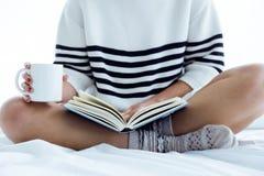 Mujer joven hermosa que lee un libro en la cama imagenes de archivo