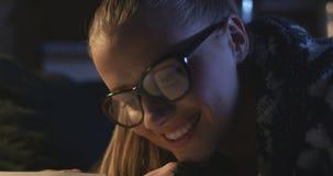 Mujer joven hermosa que lee un libro mientras que miente en el sofá metrajes