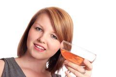 Mujer joven hermosa que levanta un vidrio de burbujeante Foto de archivo libre de regalías