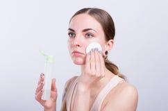 Mujer joven hermosa que limpia su cara con la esponja del algodón Imágenes de archivo libres de regalías