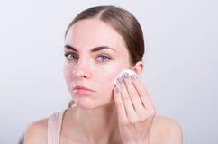 Mujer joven hermosa que limpia su cara con la esponja del algodón Imagen de archivo libre de regalías