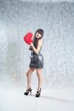 Mujer joven hermosa que lleva a cabo el corazón rojo Foto de archivo libre de regalías