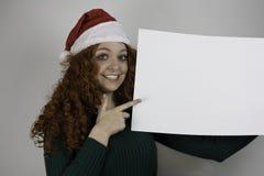 Mujer joven hermosa que lleva a cabo la muestra en blanco Imagen de archivo libre de regalías