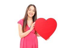 Mujer joven hermosa que lleva a cabo un corazón rojo Fotos de archivo libres de regalías
