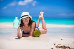 Mujer joven hermosa que lleva a cabo un suncream que miente en la playa tropical Imagen de archivo