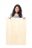 Mujer joven hermosa que lleva a cabo a una tarjeta de madera en blanco fotografía de archivo libre de regalías