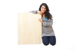Mujer joven hermosa que lleva a cabo a una tarjeta de madera en blanco Imagen de archivo