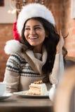 Mujer joven hermosa que lleva el sombrero rojo de Santa Claus que se sienta en el caf Imágenes de archivo libres de regalías