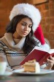 Mujer joven hermosa que lleva el sombrero rojo de Santa Claus que se sienta en el caf Foto de archivo libre de regalías