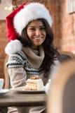 Mujer joven hermosa que lleva el sombrero rojo de Santa Claus que se sienta en el caf Fotos de archivo
