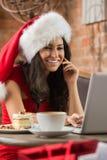 Mujer joven hermosa que lleva el sombrero rojo de Santa Claus que se sienta en el caf Imagen de archivo libre de regalías