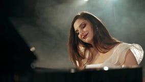 Mujer joven hermosa que lleva un vestido que hace música del piano en etapa cantidad 4k metrajes
