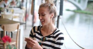 Mujer joven hermosa que mecanografía en el teléfono durante día soleado en un café del aire libre Imagenes de archivo