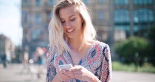 Mujer joven hermosa que mecanografía en el teléfono en una ciudad durante día soleado Imagenes de archivo