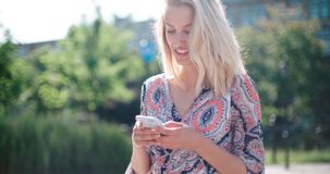 Mujer joven hermosa que mecanografía en el teléfono en una ciudad durante día soleado Fotos de archivo libres de regalías