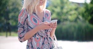 Mujer joven hermosa que mecanografía en el teléfono en una ciudad durante día soleado Imágenes de archivo libres de regalías