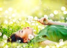 Mujer joven hermosa que miente en el campo en hierba verde y flores del diente de león que soplan imagenes de archivo
