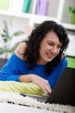 Mujer joven hermosa que miente en el piso en casa con el ordenador portátil, tipo Fotos de archivo