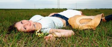 Mujer joven hermosa que miente en hierba Imagen de archivo libre de regalías