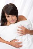 Mujer joven hermosa que miente en la cama blanca fotos de archivo