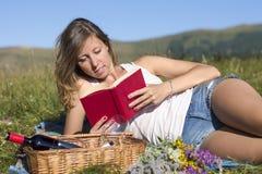 Mujer joven hermosa que miente en un prado, libro de lectura, al lado de p foto de archivo