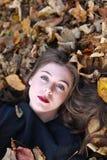 Mujer joven hermosa que miente en una cama de hojas Imagen de archivo