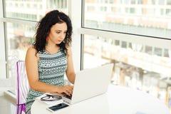 Mujer joven hermosa que mira el ordenador portátil Fotografía de archivo libre de regalías