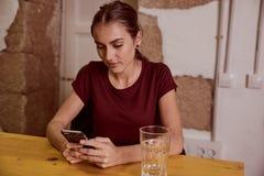 Mujer joven hermosa que mira el teléfono móvil Foto de archivo